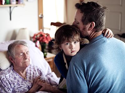 Isabel est dans son lit et, en face d'elle, se trouvent son gendre, Wayne, et son petit-fils de 4 ans, Xavier, dans la maison intergénérationnelle où ils vivent ensemble.