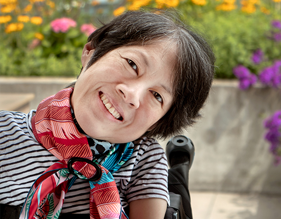 Cover image of the Canadian Institute for Health Information's report Access to Palliative Care in Canada. Ing Wong-Ward, who is currently in palliative care due to colon cancer, smiles as she sits in her wheelchair on the balcony of her Toronto apartment.