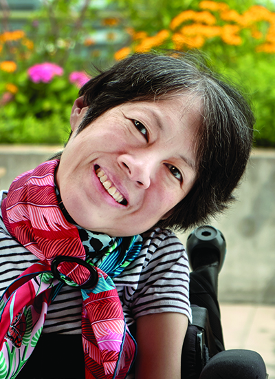 Ing Wong-Ward, who is currently in palliative care due to colon cancer, smiles as she sits in her wheelchair on the balcony of her Toronto apartment.